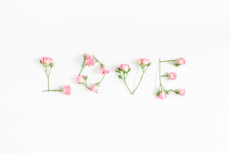 Flowers composition. Word love made of pink rose flowers on white background. Flat lay, top view