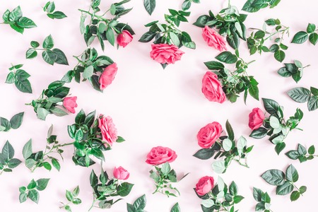 Flowers composition. Frame made of pink rose flowers on pink background. Flat lay, top view, copy space