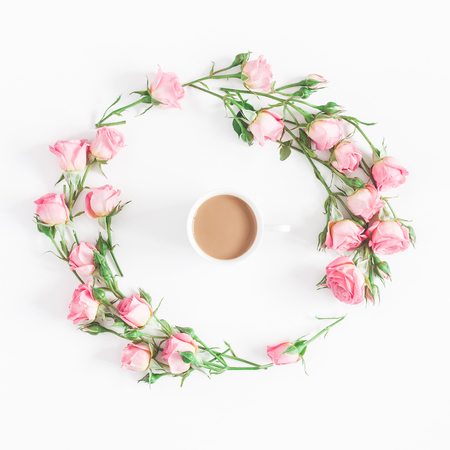 Flowers composition. Cup of coffee, pink rose flowers on white background. Flat lay, top view