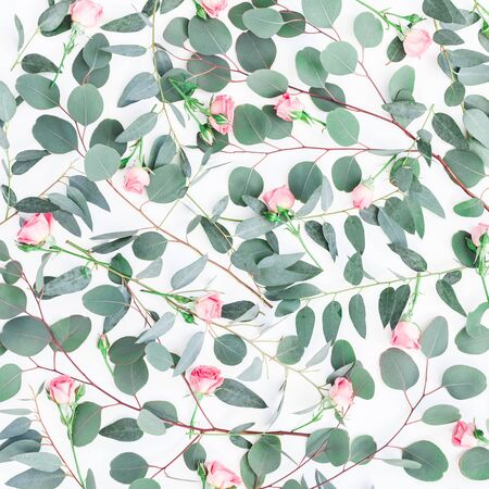 Flowers composition. Pattern made of pink rose flowers and eucalyptus branches on white background. Flat lay, top view, square Фото со стока