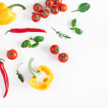 Vegetables on white background. Frame made of fresh vegetables. Tomatoes, peppers, green leaves. Flat lay, top view, copy space, square Фото со стока
