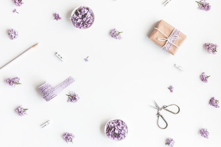 Flowers composition. Lilac flowers, gift box on white background. Flat lay, top view