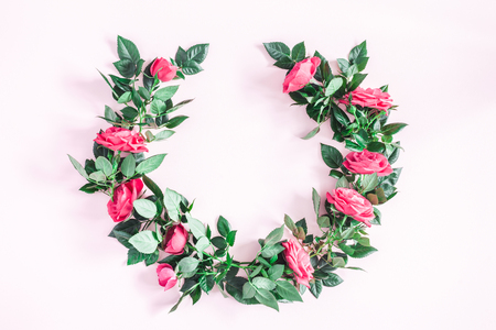 Flowers composition. Wreath made of pink rose flowers on pink background. Flat lay, top view, copy space Фото со стока