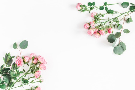 Flowers composition. Frame made of rose flowers and eucalyptus branches on white background. Flat lay, top view, copy space