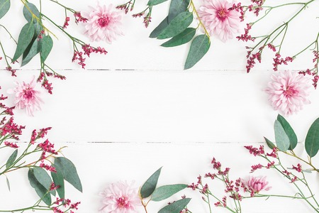 Flowers composition. Frame made of pink flowers and eucalyptus branches on white wooden background. Flat lay, top view, copy space Фото со стока