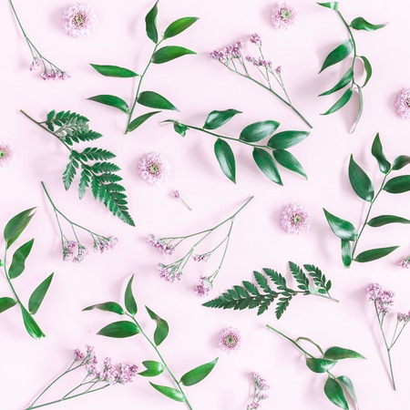 Flowers composition. Pattern made of pink flowers and green leaves on pink background. Flat lay, top view, square Фото со стока