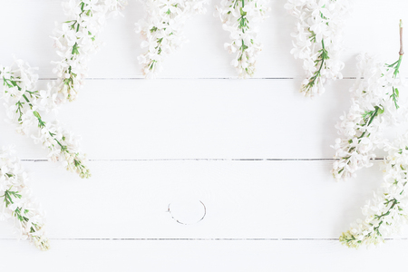 Flowers composition. Frame made of white lilac flowers on white wooden background. Flat lay, top view, copy space Фото со стока