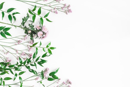 Flowers composition. Frame made of pink flowers and green leaves on white background. Flat lay, top view, copy space