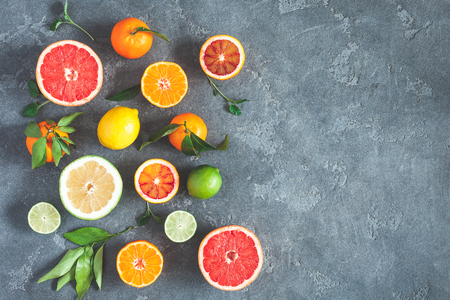 Fruit background. Colorful fresh fruits on black background. Orange, tangerine, lime, lemon, grapefruit. Flat lay, top view, copy space