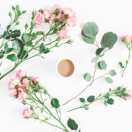 Flowers composition. Cup of coffee, pink rose flowers, eucalyptus branches on white background. Flat lay, top view, square