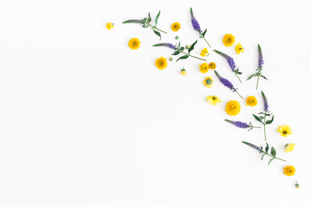 Flowers composition. Frame made of yellow, purple flowers and eucalyptus branches on white background. Flat lay, top view, copy space