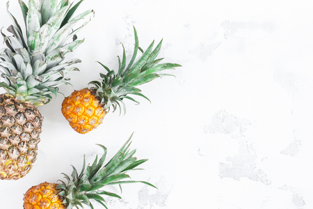 Pineapples on white background. Flat lay, top view, copy space Фото со стока