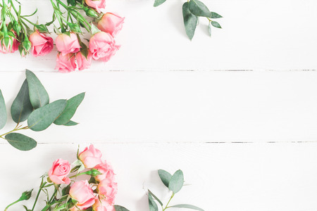 Flowers composition. Frame made of eucalyptus branches and pink rose flowers on white wooden background. Flat lay, top view, copy space Фото со стока