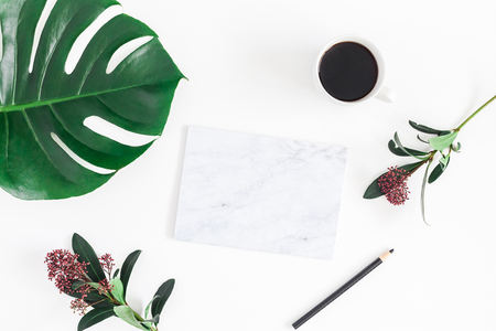 Creative workspace. Cup of coffee, tropical fllowers and leaves, marble paper blank on white background. Flat lay, top view, copy space