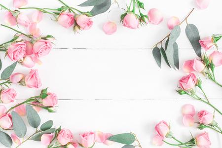 花组成。框架由粉红色的玫瑰花在白色的木制背景。平铺,俯视图,拷贝空间