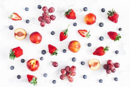 Fruit pattern. Fresh fruits Strawberry, blueberry, peach, banana, grape on white background. Flat lay, top view