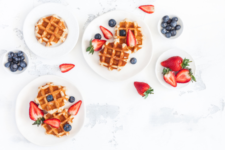 Belgian waffles with fresh strawberry and blueberry on white background. Flat lay, top view, copy space Stockfoto