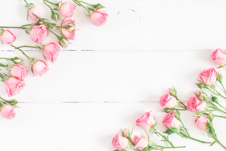 Flowers composition. Frame made of pink rose flowers on white wooden background. Flat lay, top view, copy space Stockfoto