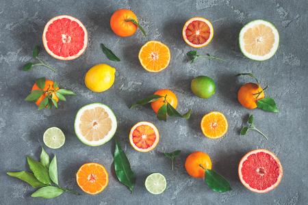 Fruit background. Colorful fresh fruits on black background. Orange, tangerine, lime, lemon, grapefruit. Flat lay, top view