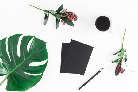 Creative workspace. Cup of coffee, tropical fllowers and leaves, marble black blank on white background. Flat lay, top view, copy space Stockfoto