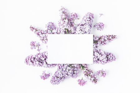 Flowers composition. Spring lilac flowers, paper blank on white background. Flat lay, top view, copy space