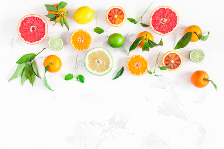 Fruit border. Colorful fresh fruits on white table. Orange, tangerine, lime, lemon, grapefruit. Flat lay, top view, copy space