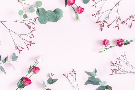 Flowers composition. Frame made of various pink flowers and eucalyptus branches on pink background. Flat lay, top view, copy space Stockfoto
