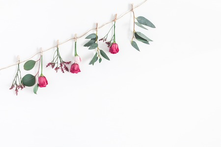 Flowers composition. Garland made of various colorful flowers and eucalyptus branches on white background. Flat lay, top view, copy space