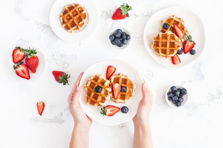 Belgian waffles with fresh strawberry and blueberry on white background. Flat lay, top view Stockfoto