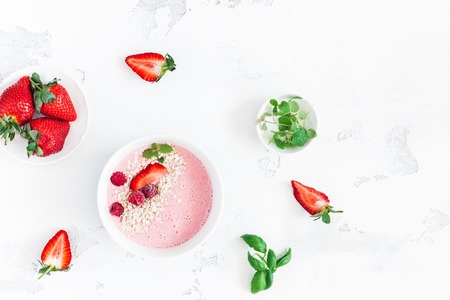 Breakfast with strawberry smoothie, fresh fruits on white background. Flat lay, top view