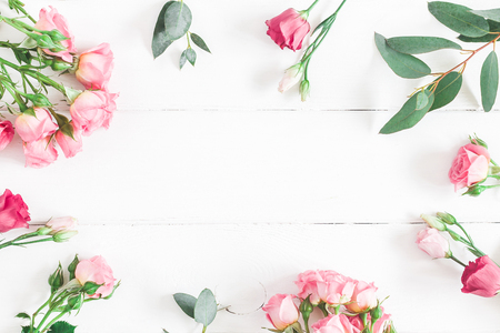 Flowers composition. Frame made of eucalyptus branches and pink rose flowers on white wooden background. Flat lay, top view, copy space Stockfoto