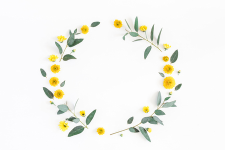 Flowers composition. Wreath made of various yellow flowers and eucalyptus branches on white background. Flat lay, top view, copy space