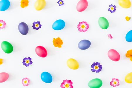 Easter eggs and primrose flowers on white background. Easter concept. Flat lay, top view