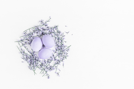 Easter eggs and purple flowers on white background. Easter concept. Flat lay, top view, copy space Stockfoto