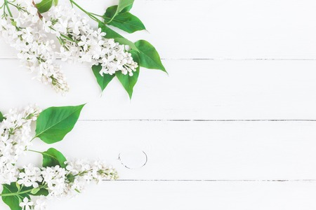 Flowers composition. Frame made of white lilac flowers on white wooden background. Flat lay, top view, copy space Stockfoto
