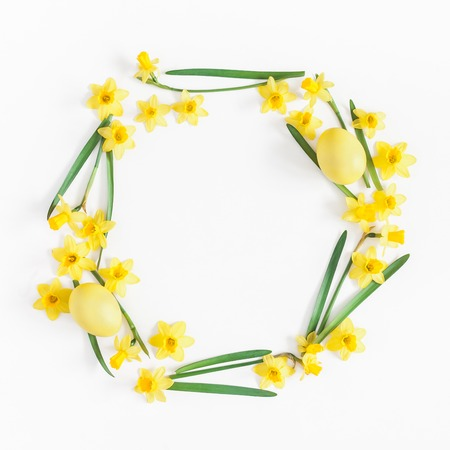Easter eggs and yellow flowers on white background. Easter concept. Flat lay, top view, copy space, square Banque d'images