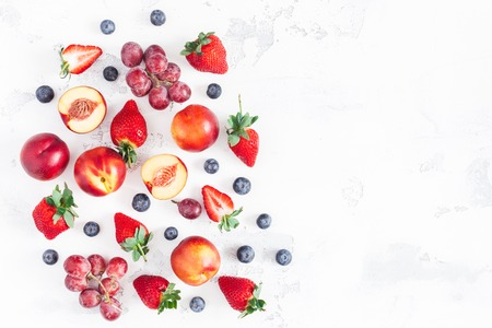 Fruit background. Fresh fruits strawberry, blueberry, peach, banana, grape on white background. Flat lay, top view, copy space