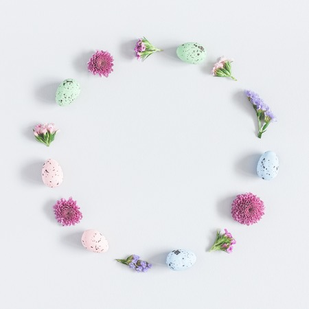 Easter eggs and colorful flowers on pastel blue background. Easter concept. Flat lay, top view, copy space, square