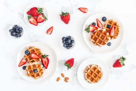 Belgian waffles with fresh strawberry and blueberry on white background. Flat lay, top view, copy space Stock Photo