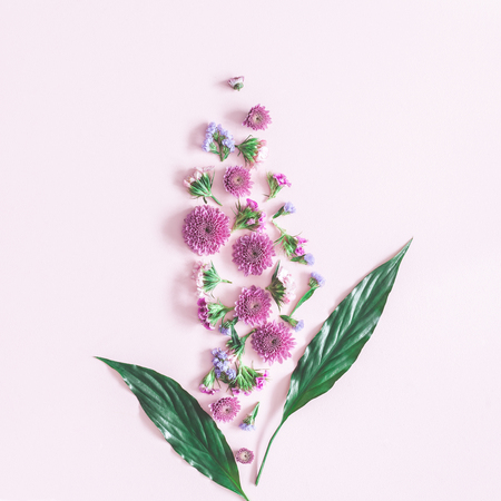 Flowers composition. Pattern made of colorful flowers and green leaves on pink background. Flat lay, top view, square