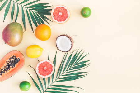 Summer tropical composition. Green palm leaves and tropical fruits on pastel yellow background. Summer concept. Flat lay, top view, copy space Stock Photo