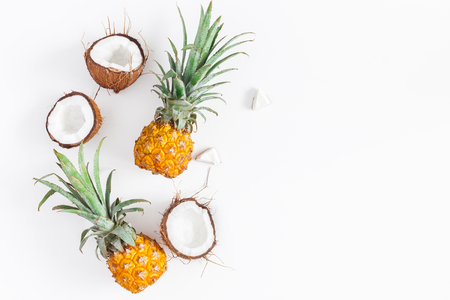Fruit background. Pineapples and coconuts on white background. Summer fruits. Flat lay, top view, copy space