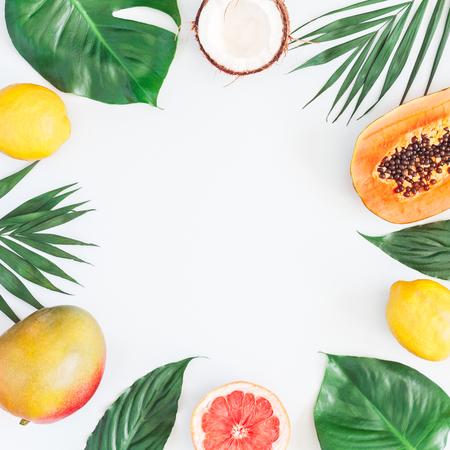 夏の熱帯の組成物。灰色の背景に緑のヤシの葉とトロピカルフルーツ。夏のコンセプト。フラットレイ、トップビュー、コピースペース
