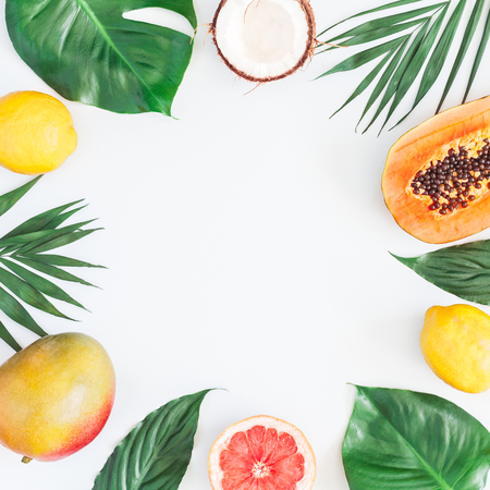 Summer tropical composition. Green palm leaves and tropical fruits on gray background. Summer concept. Flat lay, top view, copy space Foto de archivo