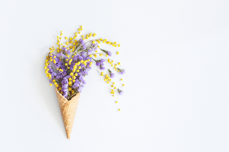 Flowers composition. Purple and yellow flowers in waffle cone. Flat lay, top view, copy space