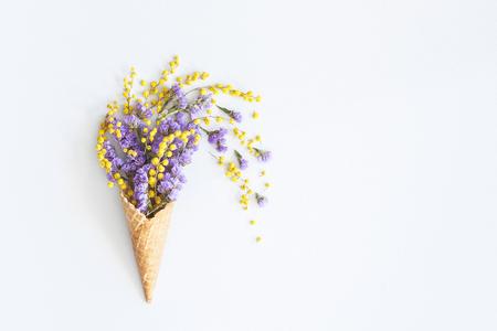 花の組成。ワッフルコーンの紫色と黄色の花。フラットレイ、トップビュー、コピースペース 写真素材
