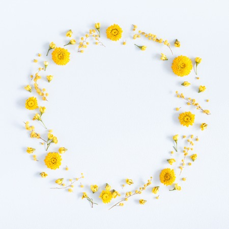 Flowers composition. Wreath made of yellow flowers on pastel blue background. Flat lay, top view, square, copy space