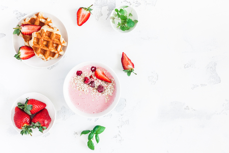 Breakfast with muesli, strawberry smoothie, waffles, fruits on white background. Flat lay, top view, copy space