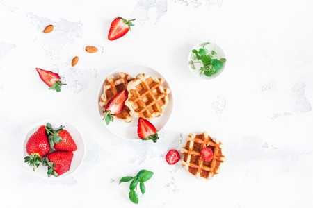 Belgian waffles with fresh strawberry on white background. Flat lay, top view