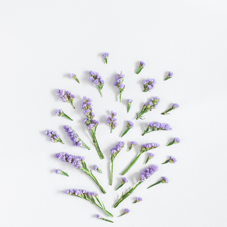 Flowers composition. Pattern made of purple flowers on pastel blue background. Flat lay, top view, square